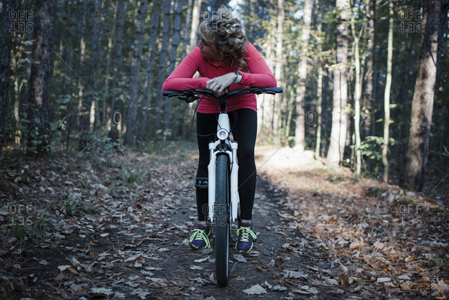 Woman sitting on mountain bike against trees in forest