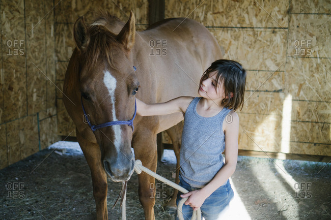 Girl petting horse while standing at barn