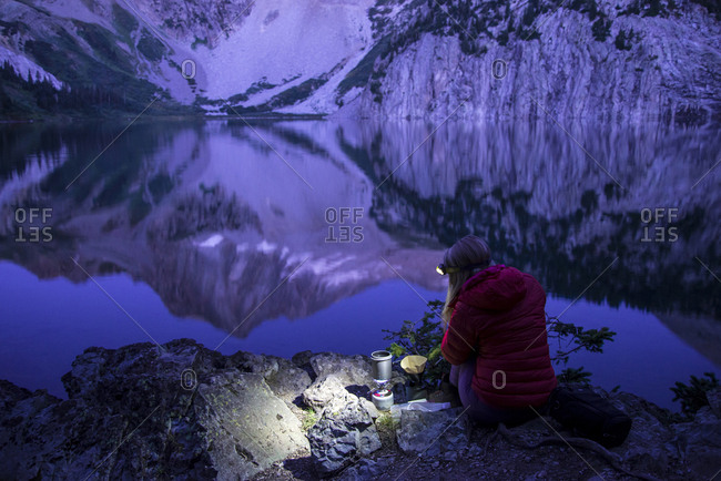 High angle view of female hiker using headlamp while making coffee by lake against mountains