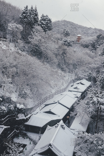 High angle view of pagoda amidst trees with snow covered houses in foreground