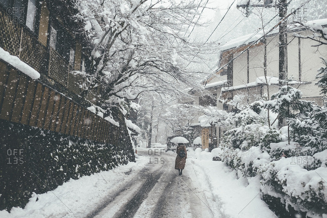 Rear view of woman holding umbrella while walking on snow covered road during snowfall in city