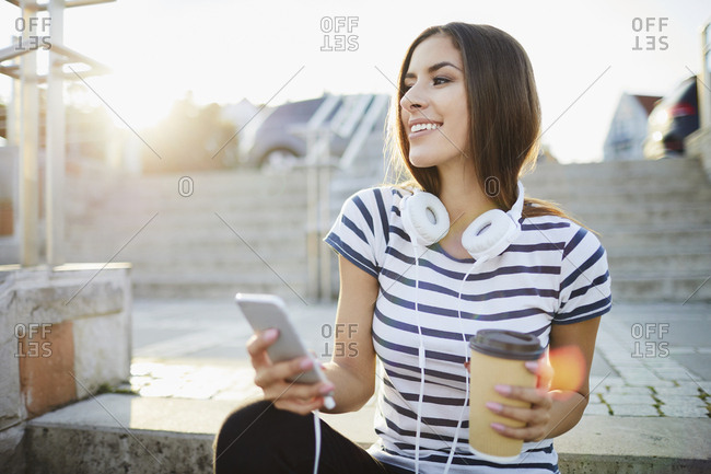 Woman with headphones sitting on stairs in the city with smartphone and coffee