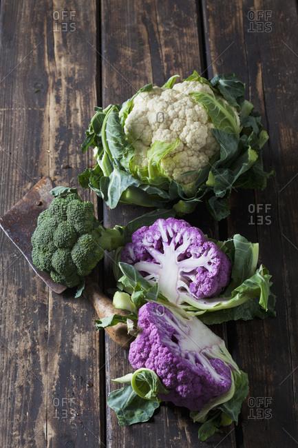 Purple and white cauliflower and broccoli on dark wood