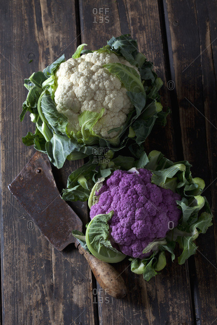 White and purple cauliflower and old cleaver on dark wood