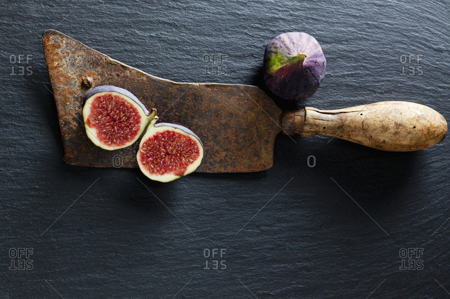 Sliced and whole fig and rusty cleaver on slate