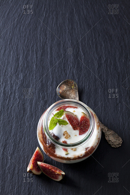 Glass of Mascarpone cream with fig compote and walnuts on slate