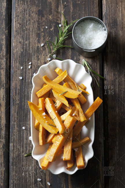 Sweet potato fries with rosemary and salt in porcelain bowl