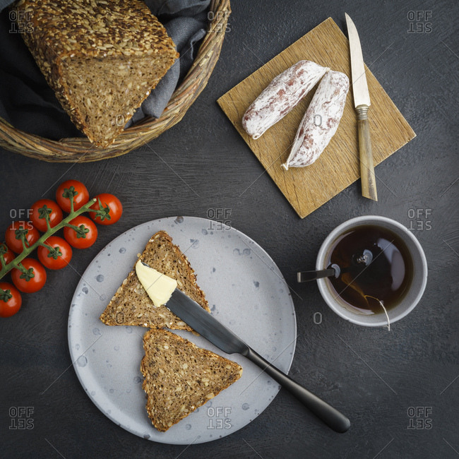 Bread with butter- cherry tomatoes- salami and cup of tea