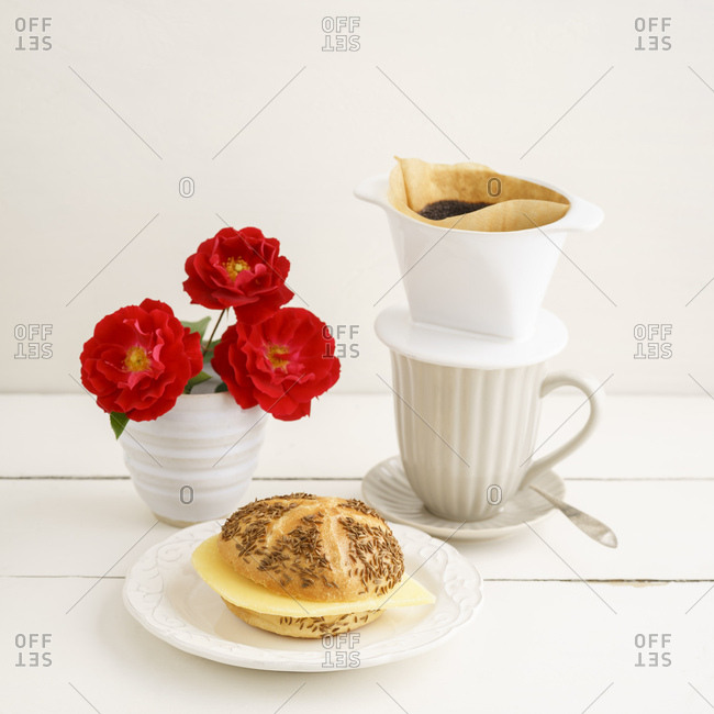 Bread roll with cheese and pour over coffee