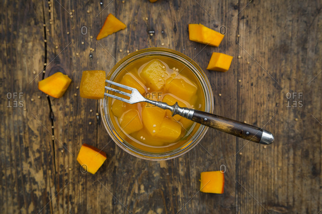 Glass of sweet-and-sour pickled pumpkin on dark wood