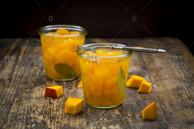 Two glasses of sweet-and-sour pickled pumpkin on dark wood