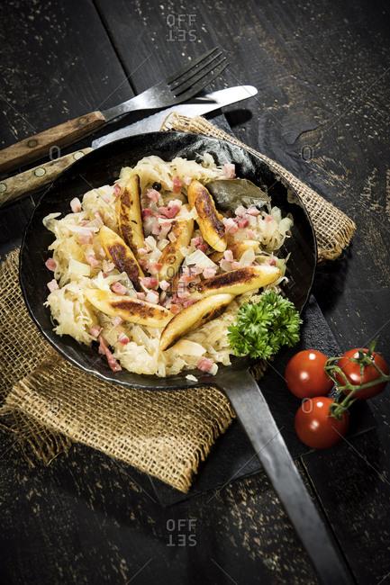 Frying pan of finger-shaped potato dumplings with sauerkraut and bacon on jute