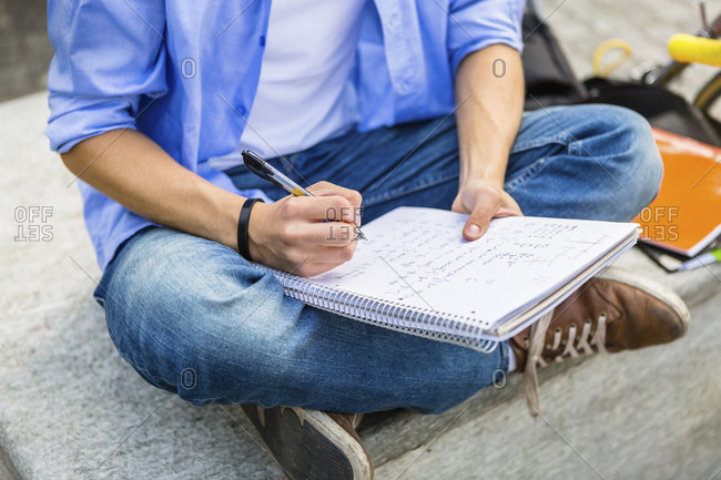 Young man sitting on bench writing on notepad- partial view