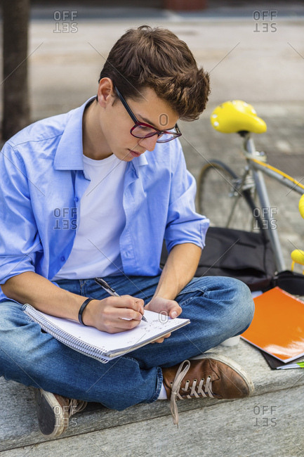Young man with racing cycle sitting on bench writing on notepad