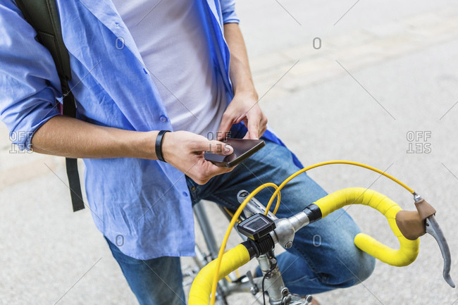Young man with racing cycle using cell phone- partial view