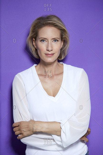 Portrait of smiling blond woman in front of purple background