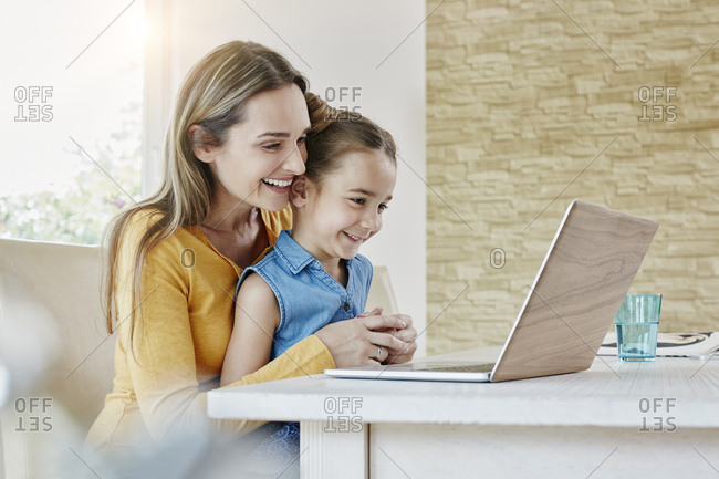 Happy mother with daughter at home looking at laptop
