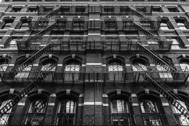 Exterior of brick building with fire escapes in New York City