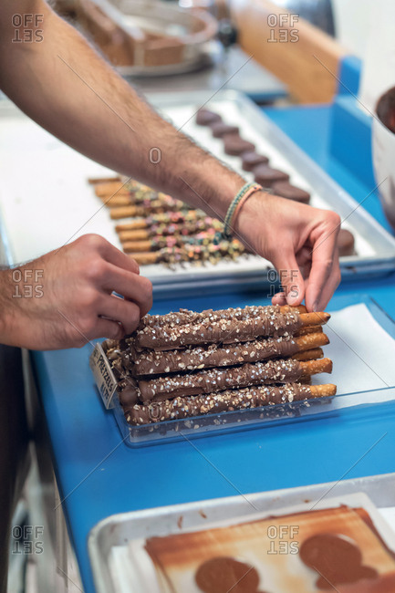 Crop confectioner serving baked sticks with chocolate in the shop.