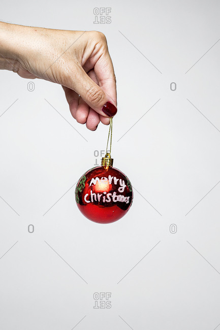 Hand of unrecognizable person holding cute red Merry Christmas ball.