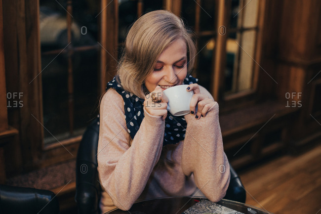 Woman cuddling with cup of tea