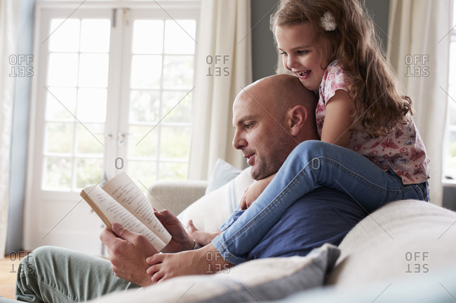 Girl on dad's shoulders while he sits reading a book at home
