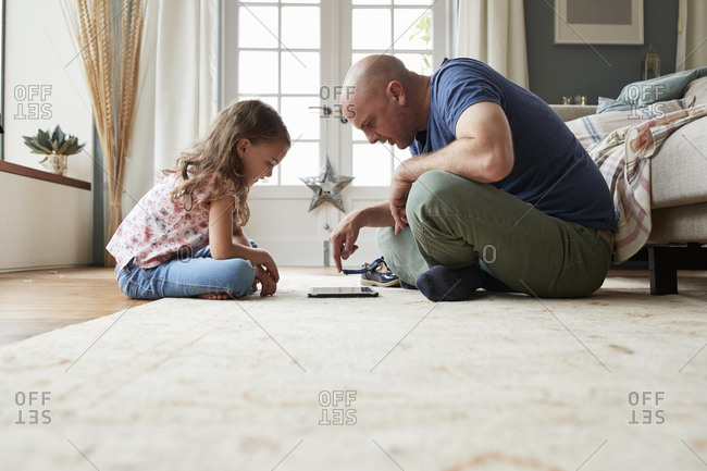 Girl and dad sit on the floor playing with tablet computer