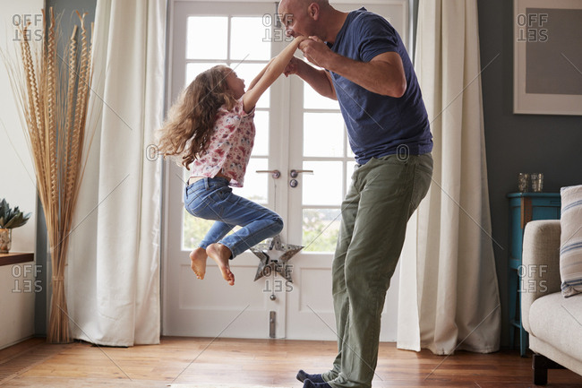 Girl jumping in the air at home holding dad's hands