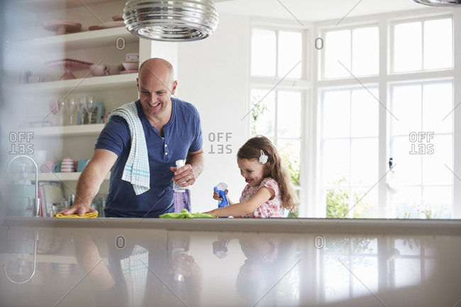 Father and daughter having fun while cleaning the kitchen