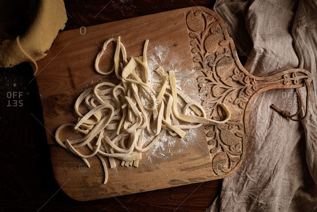 Homemade pasta noodles on a cutting board with flour