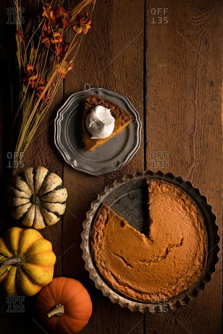 Overhead view of pumpkin pie served on a plate and gourds