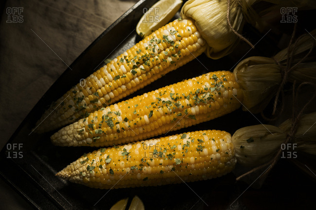 Roasted corn served on a plate with lime