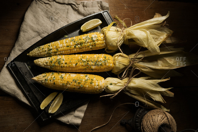 Roasted corn tied with twine and served on a plate