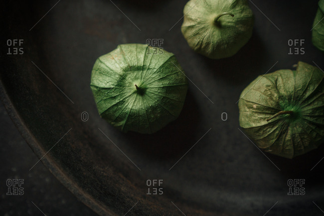 Detail of three tomatillos in a cast iron skillet
