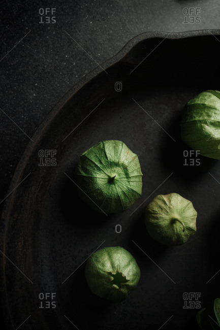 Green tomatillos in a skillet