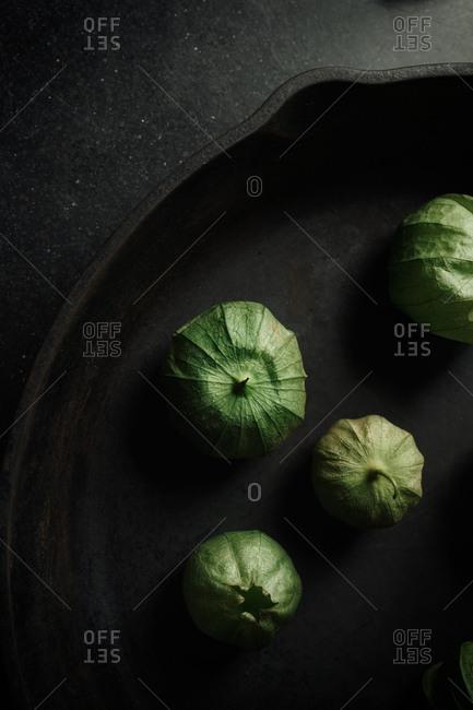 Green tomatillos in a skillet