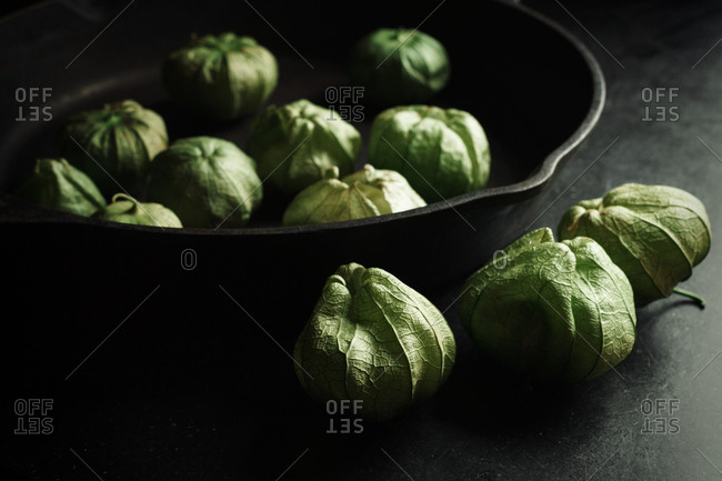 Tomatillos in and beside a skillet