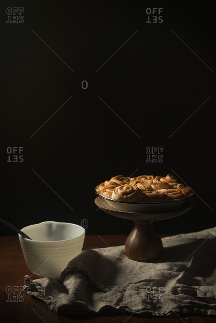 Vegan cinnamon rolls on a stand beside a bowl