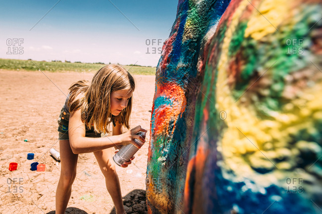 Girl spray painting a large boulder