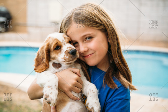 Girl holding puppy by backyard pool
