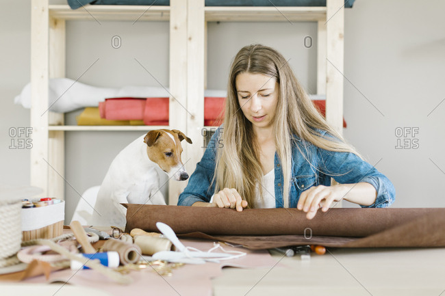 Dog watching woman work with a piece of leather