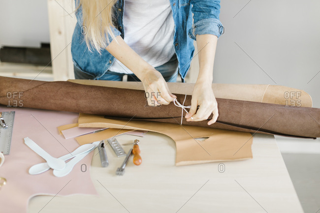 Woman tying string around a roll of leather