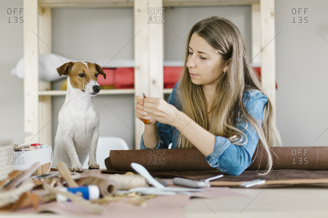 Dog watching woman use leatherworking tools