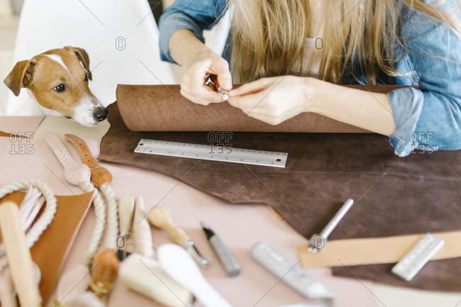 Dog watching woman with leatherworking tools