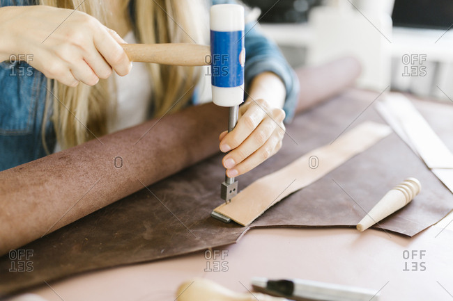 Woman using leatherworking tools to make handmade dog collar