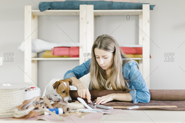 Dog watching woman cutting leather