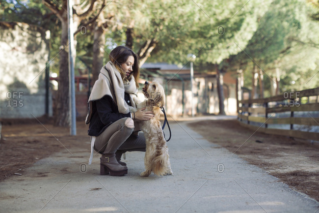 Young woman with her dog on walking path