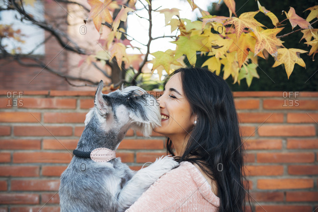 Smiling young woman nuzzling her pet dog