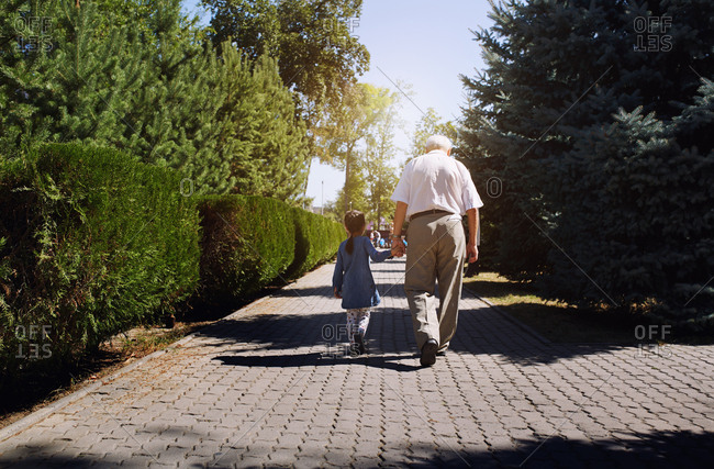 Grandfather walking with granddaughter in public park