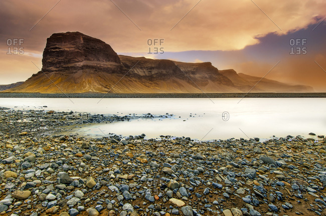 Iceland, Lomagnupur mountain, with rocks and the river in the foreground, side view